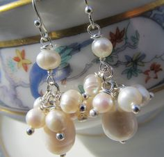 Freshwater Pearl Earrings/ BridalWedding Earrings by koatesdesigns, $28.00    Pearl bridal earrings - Wedding jewelry, Freshwater Pearls, Sterling Silver, white pearls, Handmade jewelry.    These classic pearl earrings are the perfect accessorie. The coin freshwater pearl holds a 4-5mm cluster of white freshwater pearls that dangle from a silver french wire hook with a decorative ball. These silver and pearl earrings are perfect for your wedding/bridal jewelry or any occasion.     More…