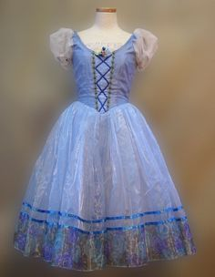 A unique creation for the role of Giselle in Act I. This Romantic tutu is created in a beautiful shade of sky blue and features a blue bodice with the typical peasant laced pattern, a round neck with