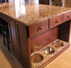 Built in Pet Food Bowls inset on the end of a Kitchen Island! Genius! #kitchentrends #romaninteriordesign #dontforgetaboutyourpetsneeds
