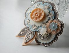 Gorgeous felt flower pin with vintage buttons in gray, aqua, and peach #diy
