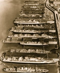A BUSY DAY IN NEW YORK HARBOUR – 1930s…The spectacular sight of 358,274 tons of shipping docked in New York Harbour. From front to back, the liners are the Hamburg, the Bremen, the Columbus, the De Grasse, the Normandie, the Britannic, the Aquitania, the Conte de Savoia, the Fort Townsend and the Monarch of Bermuda.