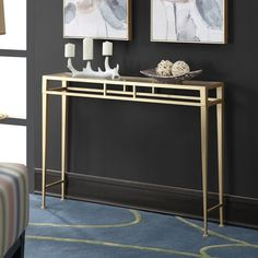 An understated canvas for framed family photos or a bowl of faux fruit, this shimmering iron console table showcases a sleek glass top and golden finish.