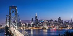 Photograph of the Bay Bridge and the San Francisco skyline lit up at dusk. Bay Bridge and SF Skyline at Dusk Wall Art By: Circle Capture from Great Big Canvas.