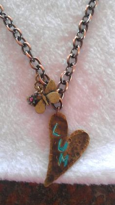 "Handmade, handstamped, Artisan Brass Heart. ""Lum"" (love you more) with butterfly charm.Each necklace, one of a kind. @www.facebook.com/T.Arch Jewelry"