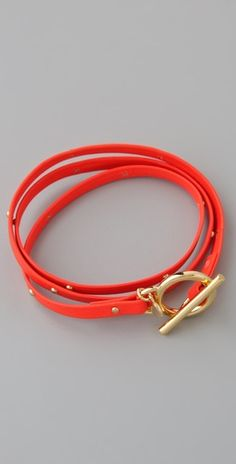 """Neon orange leather wrap bracelet w/ tiny studs and a ring-and-toggle clasp. Gold-plated hardware.  * 20"""" (51 cm) long."""