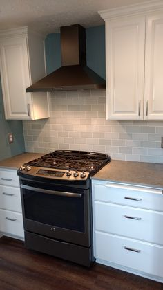 """""""Stella"""" my gorgeous gas stove sporting an attractive range hood. Loving my GE Slate appliances. Subway Tile."""