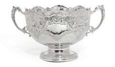 A Victorian silver two-handled rose bowl, Fenton Brothers, Sheffield, 1895the undulating rim pierced with scrolls, the body embossed with smiling masks amongst leafy scrolls and foliage, the ornate scroll handles capped with classical masks above beading, on a circular pedestal base chased with scrolling foliage