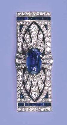 AN ART DECO SAPPHIRE AND DIAMOND BROOCH  The central oval sapphire within openwork brilliant and single-cut diamond surround to the baguette-cut sapphire and diamond line terminals, circa 1925, 6.3 cm. wide, with French assay marks for platinum and gold