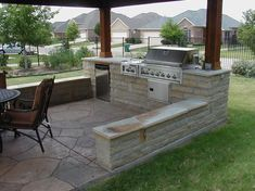 I love the idea of a pergola and stone seat surrounding the outdoor kitchen.