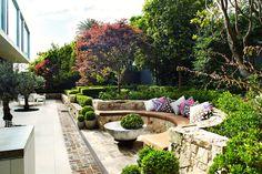 Sandstone curved seating sunken into garden - Outdoor Establishments