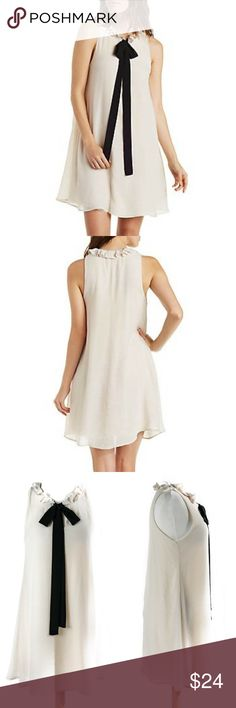 Ribbon Tie Dress Effortlessly feminine with a sweet tie front and soft ruffles around neckline. Fully lined.  100% Rayon  Color - Ivory/Black Jella Dresses Mini