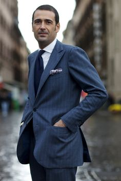 Gianluca Bocache, proprietor of Sartoria Ripense in Rome, in a pinstriped blue-grey suit, solid blue tie, white shirt, and patterned handkerchief.