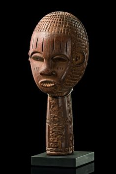 Nigeria, Izzi wood, brown patina, remains of black paint, in form of a human head rising from a long neck, both sides richly ornamented, the face shows tribe-typical facial features and parallel scarification marks in the area of forehead and cheeks. Read more: http://www.tribal-art-auktion.de/en/catalogue170/d100_301/#ixzz38ODpFKQK