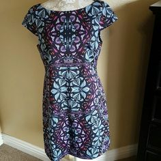 NWOT Beautiful Vince Camuto Dress Size 10 NWOT Never Worn Beautiful Vince Camuto Dress size 10 Beautiful stained glass pattern with colors of purples, blues, pinks, and orange. Flattering slightly boatneck collar with cap sleeves. Figure flattering darting at chest and waist. Exposed zipper in back Does have nice stretch and is lined scuba knit 95% Polyester 5% Spandex This is a Reposh I purchased with the tags attatched and before trying on because I love it so much I took the tags off but…