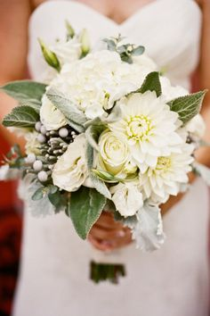The bride will carry textured bouquet of white dahlias with green buds, white fringe tulips, white lisianthus with green bud tips, white freesia with green bud tips, silver brunia, pale green succulents, gray dusty miller, and seeded eucalyptus wrapped in white ribbon with black pearl pins with the stems showing