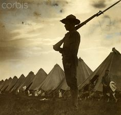 A silhouetted sentry stands guard as men move among their tents. - 42-32922144 - Rights Managed - Stock Photo - Corbis