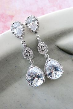 Silver Tone (Rhodium plated) cubic zirconia teardrop ear posts, collected to a vintage style rhodium cz connectors, with a luxe cubic zirconia teardrop. The luxe cubic zirconia teardrop not only has a big teardrop cz stone in the middle, but surrounded by tons of small round cubic zirconia. Seriously, how much more sparkle can we ask for. 925 sterling silver ear posts. Nickel Free. ✦ Earrings: 1.7 inch ✦ Please let me know your EVENT date when you check out. ✦ Beautifully gift wrapped in…