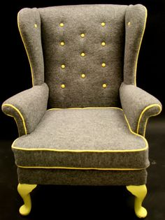 ordinary wingback reupholstered in boiled grey wool with yellow buttons and piping. this could jazz up any cheap old chair & modernize our look a bit.