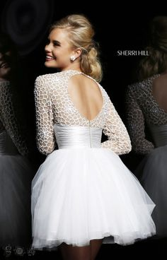 Sherri Hill 21233 is an elegant dress with many unique features! This long sleeve number has a sweetheart neckline that peeks from under the sheer overlay that is covered in white sequins. The ruched waist is perfect to show off your dangerous curves! The skirt features multiple layers of tulle to add the perfect amount of sass! 21233 is perfect for your next occasion of any kind!!