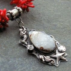 Druzy agate cabochon set in sterling silver with an oceanic theme. Hangs from a red coral necklace.