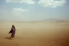 A woman holds her child close during a sandstorm in a Maasi village in the Monduli region near Arusha, Tanzania, Africa.