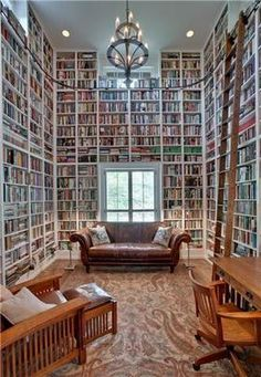 Awesome floor to ceiling book shelves. This is what I want one room to look like in my home.