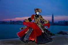 Woman wearing carnival costume along Canal di S. Marco at night