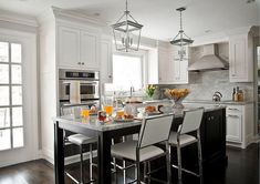 Cornice Small Lanterns light up a black center island topped with gray marble countertops paired with chrome and leather counter stools. White Leather Bar Stools, Leather Counter Stools, Kitchen Cornice, Kitchen Designs Photos, Small Lanterns, Transitional Kitchen, Marble Countertops, Gray Marble, Circa Lighting