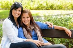 Mother and daughter relaxing on park bench happy bonding teen Stock Photo