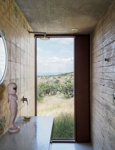 Mexican encaustic tiles with a geometric floral pattern from Mosaicos Terra line the bathroom in Austin's studio, where a full-height window near the wall-mounted shower provides a view to the expansive outdoor scenery.