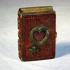 Spruce gum box with profuse chip carving and a central carved heart, likely to frame a sweetheart's photo.