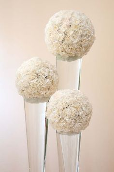 Large white pomanders of carnations balance atop towering glass vases. For the gift table , Looks like big snowballs with silver votives around bottom , kind of whimsical Carnation Centerpieces, Floral Centerpieces, Carnations, Wedding Centerpieces, Floral Arrangements, Wedding Decorations, Centrepieces, Floral Wedding, Wedding Flowers