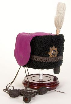 A composite Russian Imperial Life-Guard combined Cossack Regiment Enlisted man's Busby, featuring a black curled fur cap with violet wool bag with brass and enamel Guard Star plate.  Also has dark age toned silver bullion cords, flat knots and tassels, as well as an enlisted man's pattern cockade and white horse hair plume.  Restored interior with both old and new components.