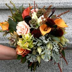 Uniquet fall color mix of peach, coral, browns and greens with silver dusty miller and succulents.