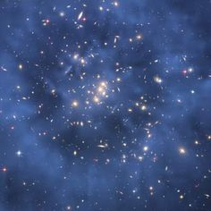 Hubble Finds Dark Matter Ring in Galaxy Cluster - The ring-like structure is evident in the blue map of the cluster's dark matter distribution. The map is superimposed on a Hubble image of the cluster. The ring is one of the strongest pieces of evidence to date for the existence of dark matter, an unknown substance that pervades the universe. ~ Credit: NASA, ESA, M.J. Jee and H. Ford (Johns Hopkins University)