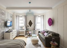 Despite being little more than a big rectangle, area rugs and wallpaper skillfully divide this studio in the Upper West Side of Manhattan into several distinct living spaces.