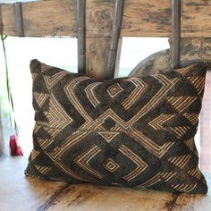 This brown and natural Kuba-cloth pillow is also known as raffia cloth. The Kuba artisans of the Congo hand cut, dye (using mud, indigo, or substances from the camwood tree), and then weave the strips of leaf to make the fabric. Small needle holes are sometimes visible from an original hand-sewn seam. Close inspection often reveals hand-sewn seams and other subtle marks from its past life. Made from vintage fabric that is approximately 50 years of age. #kuba #globaltextile