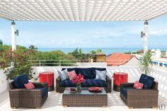 Bougainvillea and an ocean vista enliven the rooftop terrace, which is furnished with outdoor seating by Restoration Hardware and Stark fabrics of Mishaan's design.