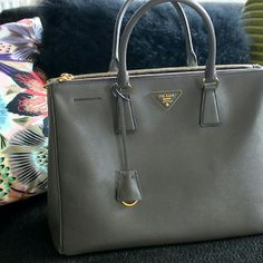 Gray prada saffiano bag Brand new with card dustbag and strap. Very stylish and fashionable bag. Classy and looks so very identical to the authentic one I paid 500 on this one but never used it. I just got authentic one so i dont need it anymore.Will be adding more pictures soon. Open to offers. Prada Bags Hobos