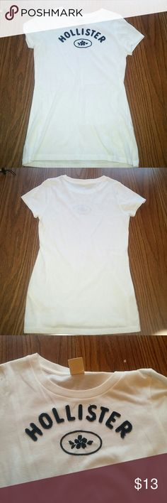 Hollister white tshirt White t-shirt with Hollister logo on chest along with a flower.  Logo and design are navy in color Hollister Tops Tees - Short Sleeve