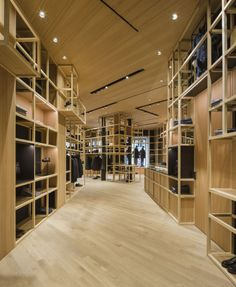 Francesc Rifé Retail. Tienda de moda Nino Fernández en Barcelona. Estructuras de madera, cristal y espejo en el antiguo Colmado Quílez. #fashion #retail #moda #interiordesign #interiorismo #glass #furniture #light. Estantes de madera para tienda de moda