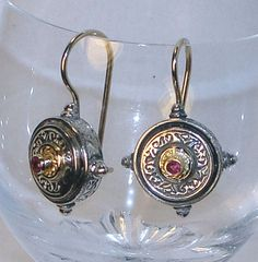 Round Ruby Wire Earrings by Konstantino 18K Gold andSterling silver dropcabochon rubyearrings.  French hook wire back withlockclasp Features beaded and floralscroll-worketching around both sides and edges. Beautifully detailed. A ruby ring in a matching style is also available.