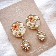 "hanauta ❁ [ accessory ] on Instagram: ""夏に向けて🌻🌻🌻    パール×ゴールドの花チャームが揺れます*    こちらは1点もので、次回のweb shop販売に出品予定です☺︎   …"" Diy Resin Art, Diy Resin Crafts, Diy Earrings Polymer Clay, Resin Jewelry, Handmade Jewelry, Resin Artwork, Resin Flowers, Jewelry Packaging, Unique Earrings"
