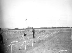 August 8, 1944 - French civilians place crosses at the graves of American soldiers in a cemetery on Omaha Beach, France.