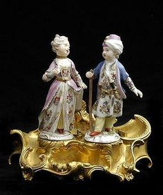 PAIR OF MEISSEN PORCELAIN FIGURES OF A BOY AND A GIRL IN NEAR EASTERN ATTIRE, MOUNTED ON LOUIS XV-STYLE GILT-BRONZE ENCRIER STAND Modeled wearing colorful clothes, the tiered scrollwork stand with various recesses, the boy with crossed swords mark; 6 3/4 x 7 1/4 in.