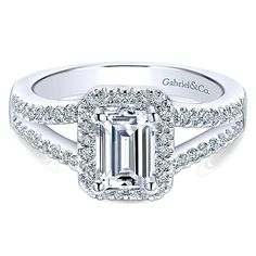 14K White Gold Emerald Cut Halo Split Shank Diamond Engagement Ring. This classic ring features .31cttw of round diamonds pave set in a split shank design with rectangular halo accenting a 1ct emerald