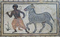 """Tesserae (mosaic stones) made of rocks from the riverbed of the Euphrates were used to depict a black man leading a zebra. The 5-6 th century floor mosaic can be found in the """"Villa of the Amazons"""", a palatial house, that probably belonged to an important administrator of the Eastern Roman (Byzantine) Empire, who lived in Edessa (nowadays called Urfa). Aleppian Gardens (Haleplibahçe), Edessa, Şanlıurfa Turkey."""