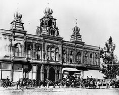 (1890)* - View of the ornate facade of the Pasadena Grand Opera House with horses and carriages in front.