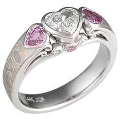 Mokume Carved Curls Three Stone Engagement Ring - Similar to its predecessor, the Carved Curls Engagement Ring, this luxury ring's band is inlaid with mokume gane. The pricing calculator does not include the side stones, and the ring is priced out with white diamond round accents stones.    - This ring has a heart-shaped diamond and two pink sapphires. The band is inlaid with Champagne mokume that is etched.