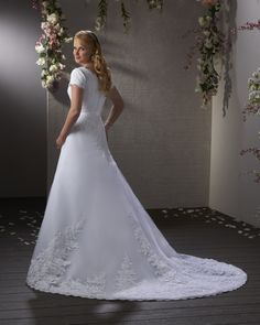 Bonny 2401 - This demure gown has a corded lace bodice with a grosgrain ribbon belt wrapping around the waist. The sequin lace edges the hem of the trumpet shaped skirt and train. $1190.00